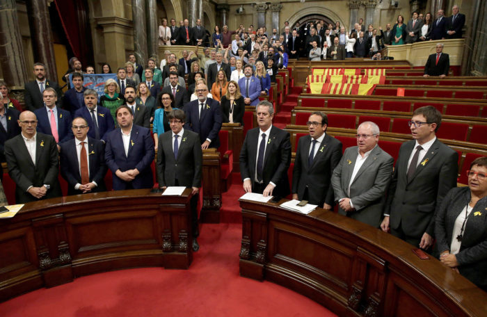 Barcelona, 2017. október 27. Carles Puigdemont katalán elnök (b4) és Oriol Junqueras alelnök (b3) éneklik a nemzeti himnuszt a katalán parlament üléstermében Barcelonában 2017. október 27-én, miután a katalán parlament függetlenségi pártjai megszavazták a független Katalán Köztársaság létrehozását célzó javaslatot. Az ellenzéki Ciudadanos (Állampolgárok) nevű liberális középutas párt, a Katalán Szocialista Párt (PSC) és a Spanyolországban kormányzó konzervatív Néppárt (PP) képviselői a szavazás előtt elhagyták az üléstermet, utóbbiak előtte padjaikat spanyol és katalán zászlókkal terítették le.(MTI/EPA/Alberto Estevez)