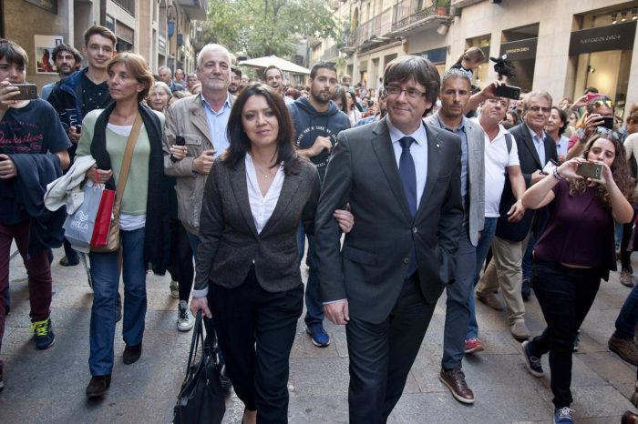 """Girona, 2017. október 28. Carles Puigdemont leváltott katalán elnököt (k, jobbra) és feleségét, Marcela Toport kísérik támogatók Gironában 2017. október 28-án, egy nappal az után, hogy Mariano Rajoy spanyol miniszterelnök menesztette őt a spanyol szenátustól kapott felhatalmazás alapján. Puigdemont televíziós nyilatkozatában """"demokratikus ellenállásra"""" szólított fel a spanyol alkotmány 155-ös cikkének alkalmazásával szemben. A spanyol kormány megkezdte a katalán kormányzati feladatok átvételét, a katalán elnöki jogkörök gyakorlásával Soraya Sáenz de Santamaría spanyol miniszterelnök-helyettest bízta meg Rajoy. (MTI/EPA/Robin Townsend)"""