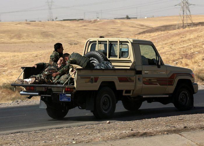 Alton Kupri, 2017. október 20. Sebesült társukat viszik kórházba kurd fegyveresek egy autóplatón az észak-iraki Erbíl város közelében fekvő Alton Kupri felé az iraki hadsereggel vívott függetlenségi harcok idején, 2017. október 20-án. (MTI/AP/Halid Mohamed)