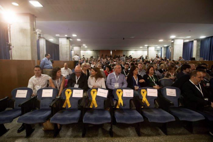 Barcelona, 2017. november 5. Az európai elfogatóparancs alatt álló Antoni Comin, Lluis Puig, Meritxell Serret és Clara Ponsati volt katalán kormánytagok üres helyét jelképező sárga szalagok a függetlenségpárti Európai Katalán Demokrata Párt (PDeCAT) ülésén Barcelonában 2017. november 5-én. Ezen a napon a Spanyolországban lázadással, zendüléssel és hűtlen kezeléssel vádolt Carles Puigdemont menesztett katalán elnök feladta magát a belga rendőrségen. (MTI/EPA/Marta Pérez)