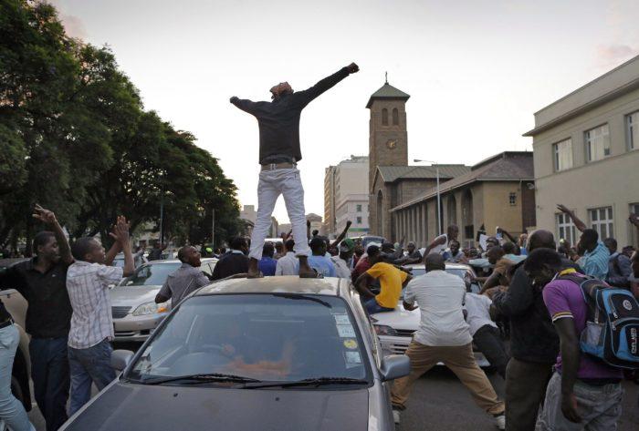 Harare, 2017. november 21. Ünneplő emberek a hararei parlament előtt 2017. november 17-én, miután Jacob Francis Mudenda, a zimbabwei törvényhozás házelnöke bejelentette, hogy Robert Mugabe megbuktatott elnök lemondott. (MTI/EPA/Kim Ludbrook)