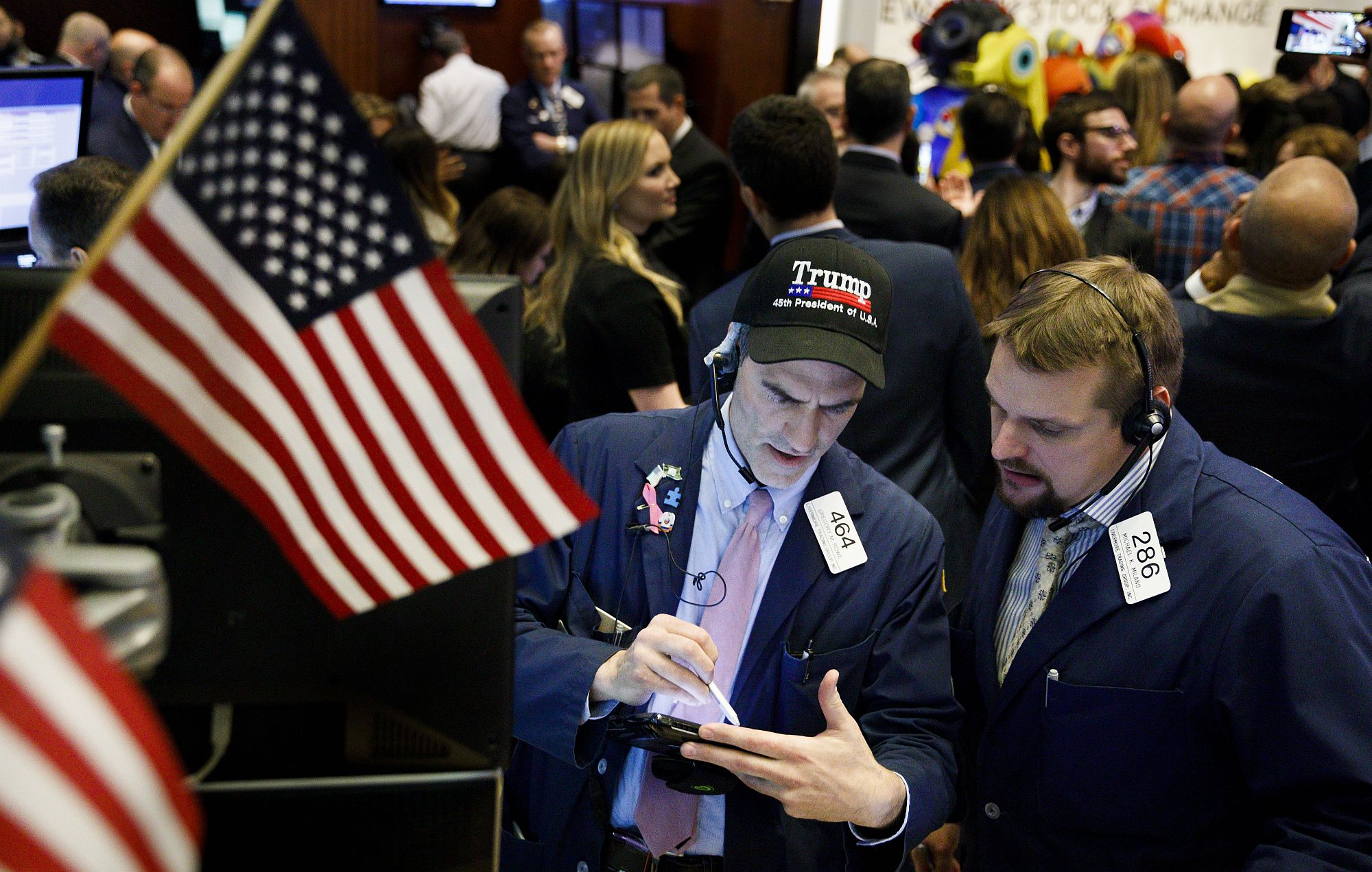 Tőzsdei kereskedő Trump sapkában a New York-i Értéktőzsdén 2017. november 30-án a kereskedési nap végén, miután a Dow Jones index először lépte át a 24.000 ponto szintet. EPA/JUSTIN LANE