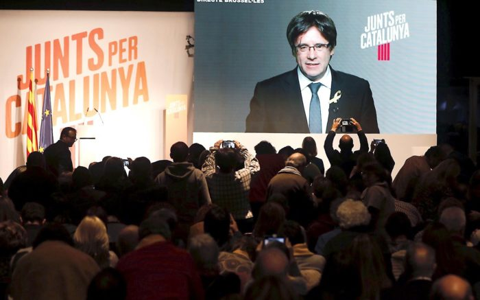 epa06397810 Junts per Catalunya's candidate and former Catalonia's president Carles Puigdemont (at the screen) speaks during a videoconference from Brussels during an electoral campaign event in Lleida, Catalonia, Spain, 18 December 2017. Catalan regional elections will be held on 21 December 2017, as the Spanish central government applied article 155 of the Constitution after the regional Parliament declared the unilateral declaration of independence on 27 October 2017. EPA/Juan Carlos Cardenas