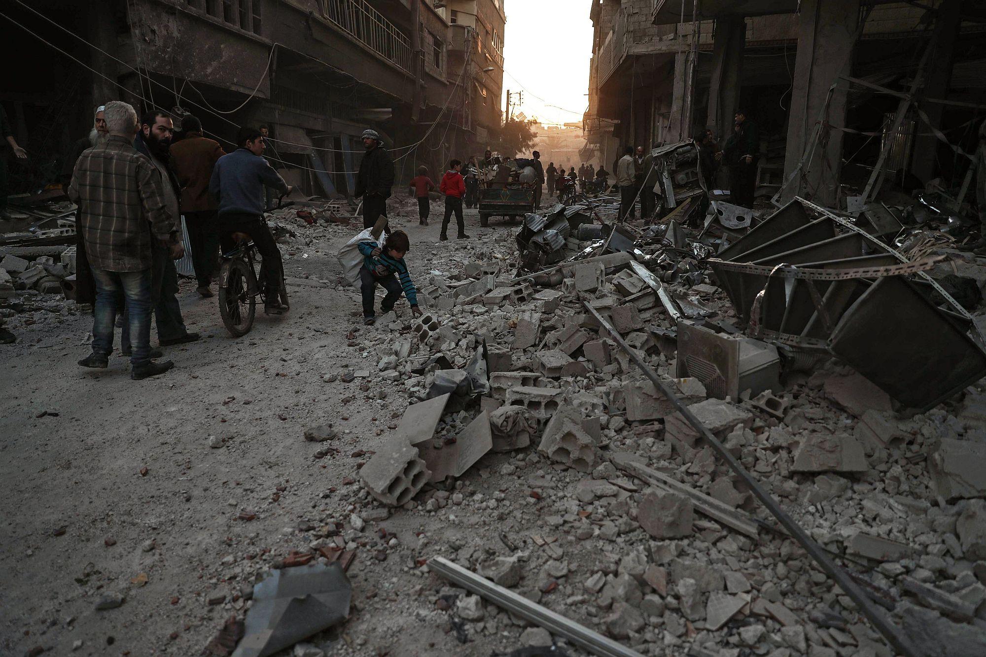 A pusztítás nyomait nézik emberek a szíriai főváros, Damaszkusz Hamoria nevű külvárosában 2017. december 3-án, a szíriai kormánnyal szövetséges erők újabb légicsapása után. A bombázásban legkevesebb 17 ember életét vesztette. (MTI/EPA/Mohamed Badra)
