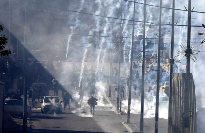 Palesztin tüntetők menekülnek az izraeli rendőrök által feléjük lőtt könnygázgránátok elől a ciszjordániai Betlehemben vívott összecsapásuk közben 2017. december 9-én. Három nappal korábban Donald Trump amerikai elnök bejelentette, hogy az Egyesült Államok Tel-Aviv helyett Jeruzsálemet tekinti Izrael fővárosának. Trump bejelentésére számos muszlim ország felháborodottan reagált, a Hamász palesztin mozgalom, amely a Gázai övezetet uralja, egyenesen felkelésre (intifádára) szólított fel. (MTI/EPA/Abed al-Haslamun)