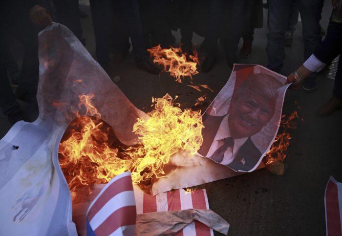 Gáza, 2017. december 7. Donald Trump amerikai elnököt ábrázoló plakátot égetnek palesztinok Gázában 2017. december 7-én, egy nappal azután, hogy Trump aláírta a Jeruzsálemet Izrael fővárosaként elismerő dekrétumot. Trump bejelentette továbbá, hogy Tel-Avivból Jeruzsálembe helyezteti át az amerikai nagykövetséget. (MTI/AP/Halil Hamra)