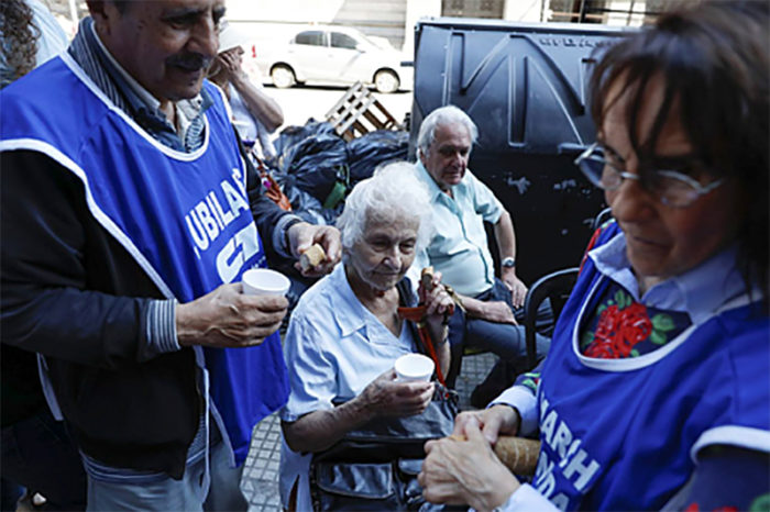 epa06400616 A group of retirees make a toast with bread and water in front of the headquarters of the Congress in Buenos Aires, Argentina, on 20 December 2017, in rejection of the recently approved pension reform. EPA/David Fernández