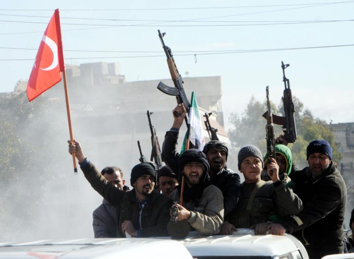 epa06454810 Members of Free Syrian Army (Turkey-backed) fighters tour with their guns as they hold Turkish and their flag in the Syria city of Azez, near the Syrian-Turkish border, 19 January 2018. Report state that the Turkish army is preparing for an operation in Syria against the Kurdish Popular Protection Units (YPG) forces. EPA/HASAN KIRMIZITAS