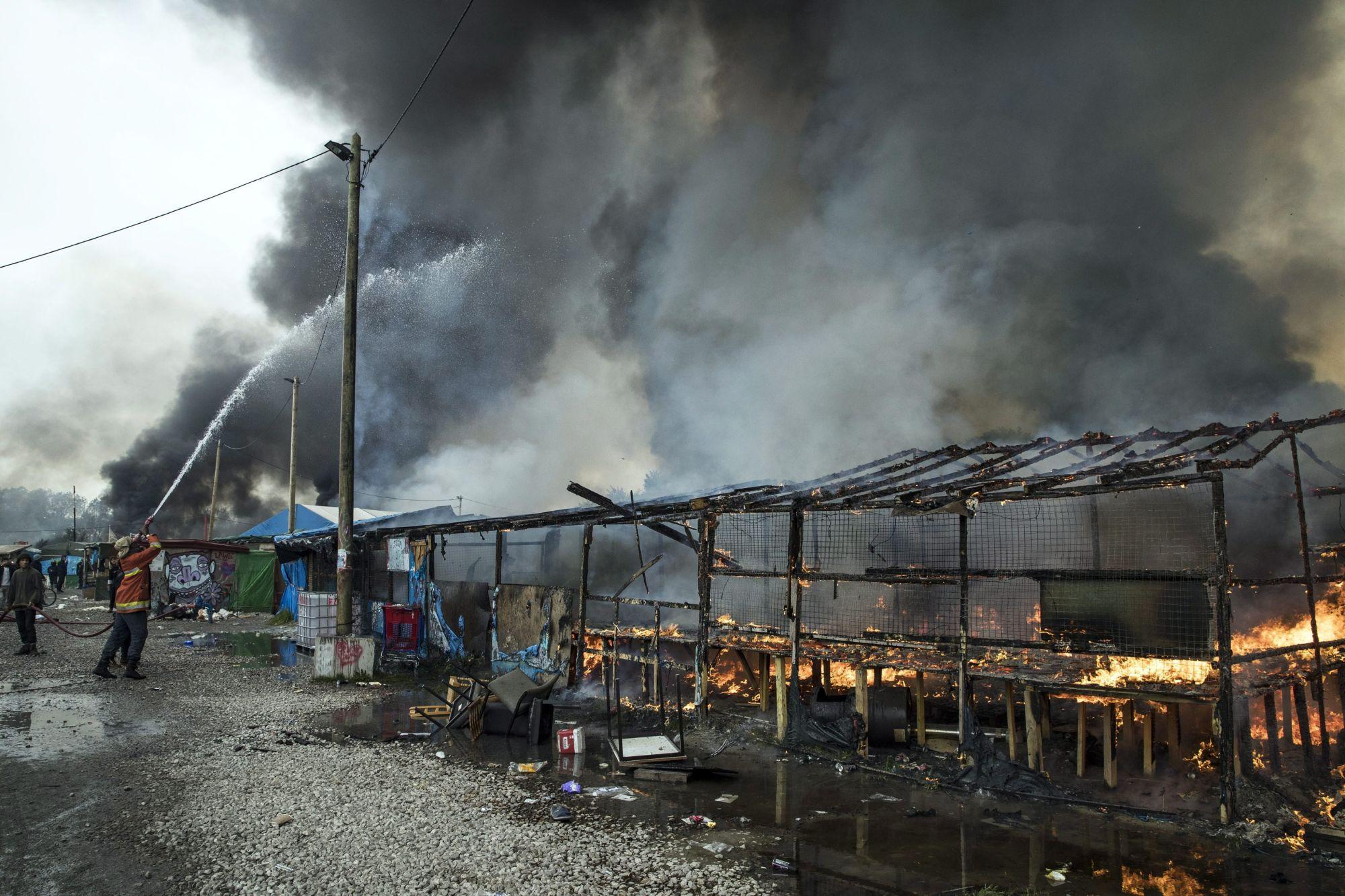 Calais, 2016. október 26. Tűzoltó harcol a lángokkal távozó migránsok által felgyújtott bódék füstölgő maradványainál az észak-franciaországi Calais-ban engedély nélkül létesített szükségtábor bontási munkálatai alatt 2016. október 26-án. A francia hatóságok két nappal korábban kezdték meg a Dzsungelnek nevezett tábor felszámolását, a kiürítés a tervek szerint egy hét alatt lezajlik. (MTI/EPA/Etienne Laurent)