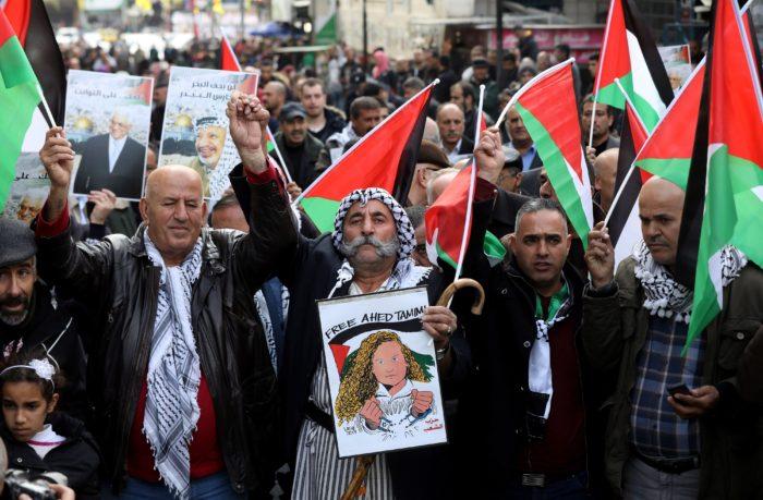 Náblusz, 2017. december 31. Palesztin tüntetők a ciszjordániai Nábluszban 2017. december 31-én. A tüntetők Donald Trump amerikai elnök döntése miatt tiltakoztak, amely szerint az Egyesült Államok Tel-Aviv helyett Jeruzsálemet tekinti Izrael fővárosának. A plakát Ahed Tamimi palesztin aktivista szabadon bocsátását követeli. (MTI/EPA/Abed al-Haslamun)