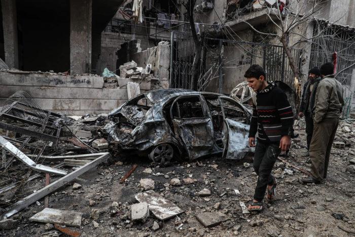 Hamúria, 2018. január 7. Megsemmisült épületek romjai közt mennek emberek a felkelők kezén lévő szíriai Hamúria városában 2018. január 6-án. Legkevesebb 17 civil vesztette életét a szíriai fővároshoz közeli, ostromlott kelet-gútai térségben az orosz légierő legutóbbi csapásai következtében. (MTI/EPA/Mohammed Badra)