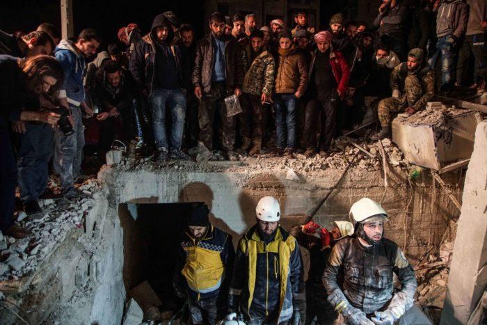 Idlíb, 2018. január 8. Civilek nézik, amint a mentőegységek tagjai túlélők után kutatnak a romok közt a szíriai ellenzék kezén lévő legnagyobb városban, Idlíbben 2018. január 8-án, miután autóba rejtett pokolgép robbant a csecsenek vezette Adzsnad al-Kavkaz (Kaukázus katonái) iszlamista csoport főhadiszállása közelében. A támadásban legkevesebb tizennyolcan életüket vesztették, több tucatnyian megsebesültek. (MTI/EPA/Jahja Nemah)