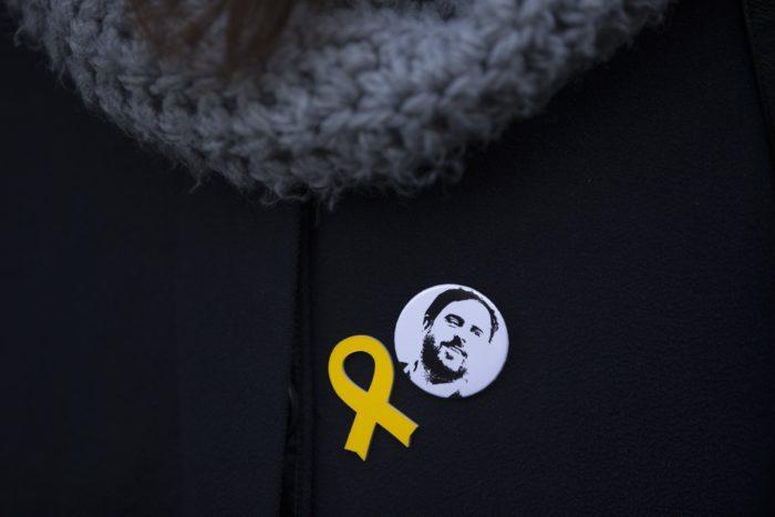 Madrid, 2018. január 11. Oriol Junqueras volt katalán alelnököt, a függetlenségpárti Katalán Köztársasági Baloldal (ERC) bebörtönzött vezetőjét ábrázoló kitűző a katalán politikai foglyok jelképévé vált sárga szalag mellett egy támogató kabátján a madridi legfelsőbb bíróság épületénél 2018. január 11-én, Joaquim Forn volt katalán belügyminiszter, valamint Jordi Sánchez és Jordi Cuixart bebörtönzött függetlenségpárti vezetők meghallgatása napján. Két nappal korábban Carles Puigdemont leváltott katalán elnök újraválasztásáról kötött megállapodást a két legnagyobb katalán függetlenségi párt, az ERC és az Együtt az Igenért (Junts pel Sí). (MTI/AP/Francisco Seco)