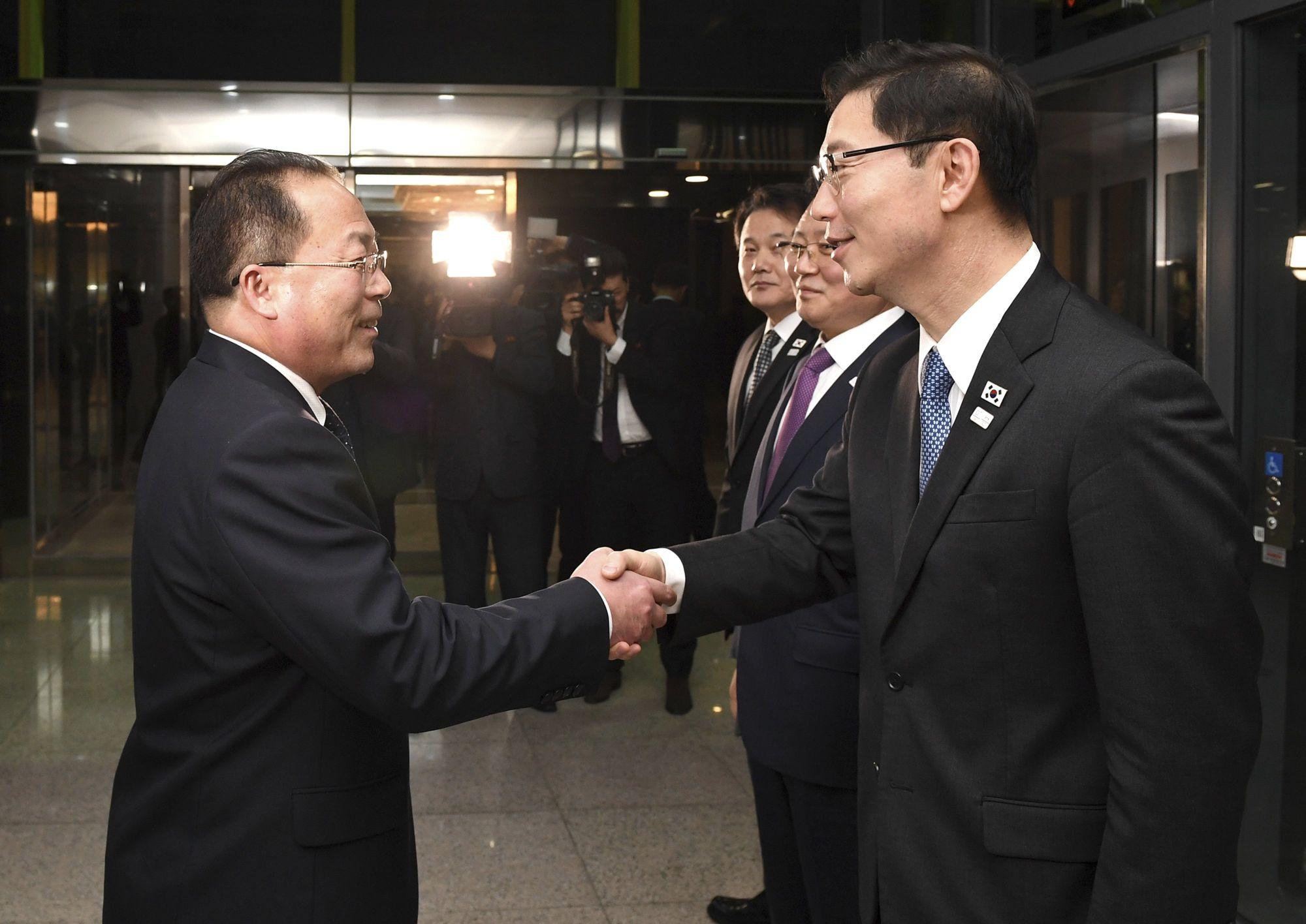 A dél-koreai egyesítési minisztérium által közreadott képen Csun He Szung dél-koreai egyesítési miniszter-helyettes (j) és Dzson Dzsong Szu, az észak-koreai delegáció vezetője kezet fog a februári dél-koreai téli olimpián való észak-koreai részvételről tartott tárgyalás következő fordulója után a két Koreát elválasztó panmindzsoni demilitarizált övezet dél-koreai oldalán 2018. január 17-én. A felek megállapodtak abban, hogy Phenjan sportolókat, magas rangú tisztviselőket és szurkolókat küld a téli olimpiára. (MTI/AP/Dél-koreai egyesítési minisztérium)