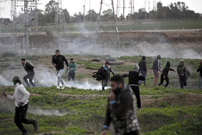 Gáza, 2018. január 27. Palesztin tüntetők futnak az feléjük dobott könnygázgránátok elől a Donald Trump amerikai elnök Jeruzsálem státuszáról tett döntése elleni tiltakozáson Gázában 2018. január 27-én. Trump december 6-án bejelentette, hogy az Egyesült Államok Tel-Aviv helyett Jeruzsálemet tekinti Izrael fővárosának. (MTI/EPA/Mohamed Szaber)