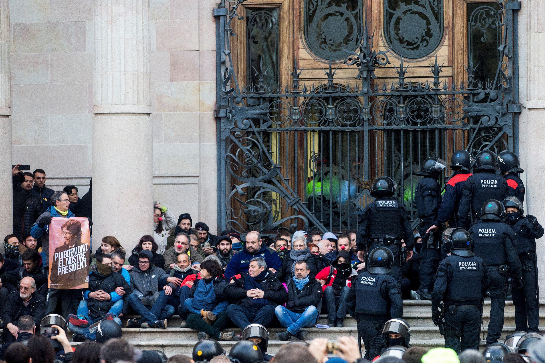 Barcelona, 2018. február 23. Katalán rendőrök érkeznek Carles Puigdemont leváltott katalán elnök támogatóinak a bebörtönzött függetlenségpárti katalán politikusok szabadon bocsátását követelő ülőtüntetésére a katalán legfelsőbb bíróság (TSJC) barcelonai épületénél 2018. február 23-án. (MTI/EPA/Quique García)