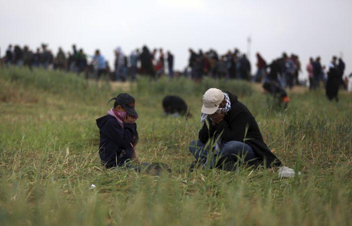 Palesztin tüntetők izraeli katonák által kilőtt könnygáz ellen próbálnak védekezni a palesztinok lakta Gázai övezetet Izraeltől elválasztó határkerítésnél, Gáza város keleti peremén 2018. március 30-án.  (MTI/AP/Halil Hamra)