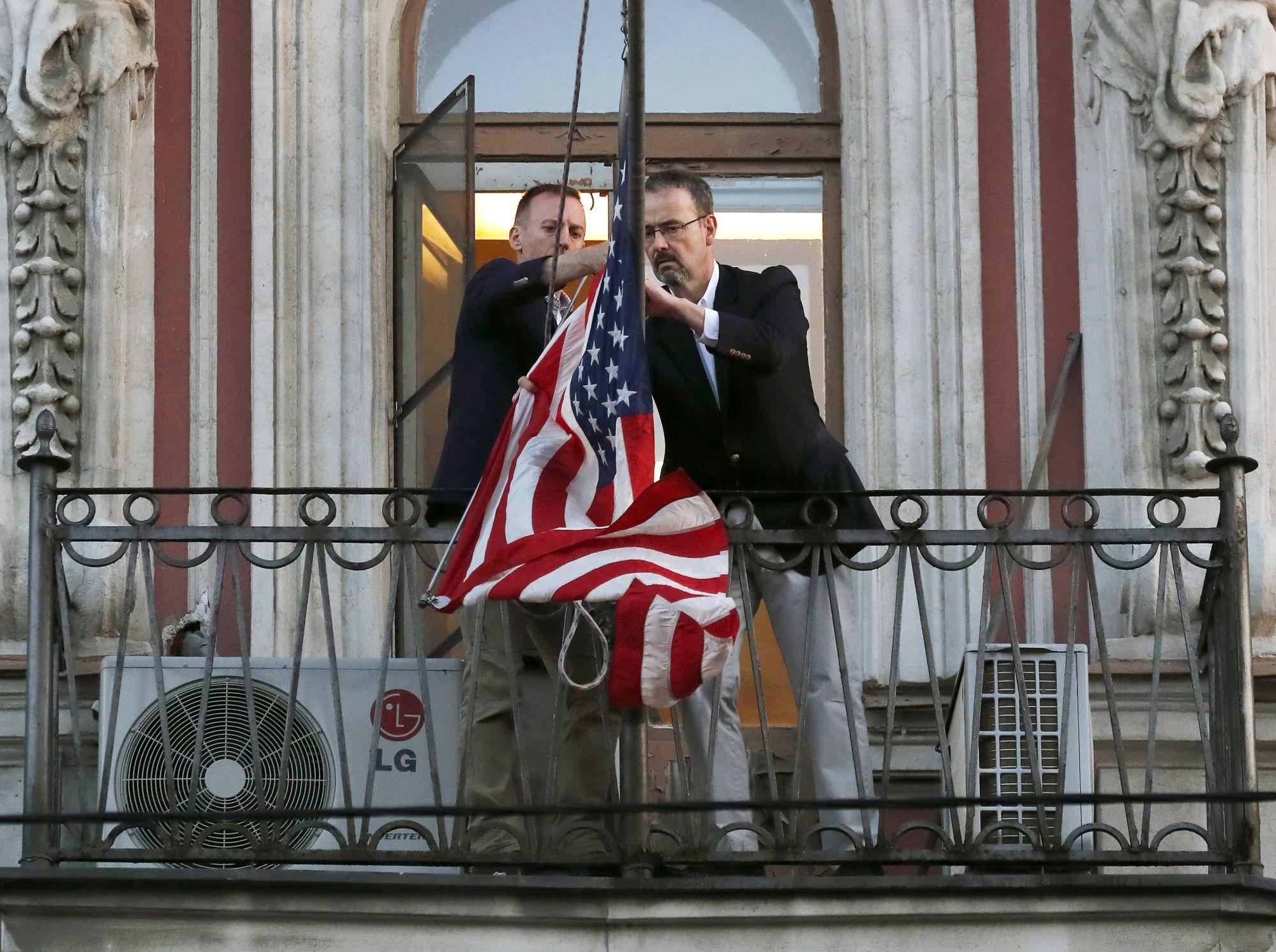 A szentpétervári amerikai konzulátus munkatársai leveszik az amerikai zászlót 2018. március 31-én. Az amerikai szankciókra válaszul Oroszország 60 amerikai diplomatát utasított ki és a szentpétervári konzulátus bezárásáról döntött. Az orosz hatóságok két napot adtak az épület teljes kiürítésére. EPA/ANATOLY MALTSEV