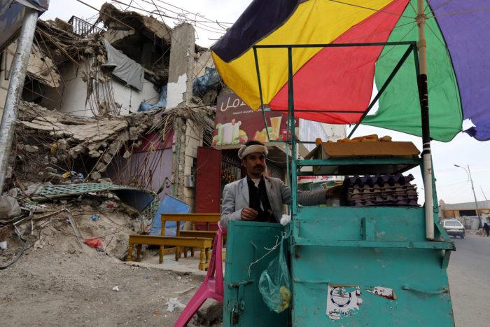 Szanaa, 2018. április 17. Élelmiszert árul egy jemeni férfi a Szaúd-Arábia vezette nemzetközi koalíció által korábban lebombázott épületek egyike előtt a fővárosban, Szanaában 2018. április 16-án. Jemeni síita lázadók április 11-én több ballisztikus rakétát is kilőttek különböző szaúd-arábiai célpontokra. A szaúdi légvédelem az egyik rakétát Rijád felett lőtte le. (MTI/EPA/Jahja Arhab)