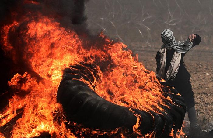 Gáza, 2018. április 20. Palesztin tüntető követ hajít égő gumiabroncsok mellett a határkerítés túloldalán levő izraeli katonák felé Gáza városától keletre 2018. április 20-án. A Gázai övezetet uraló Hamász radikális iszlamista szervezet április eleji felhívására a palesztinok hat héten át tiltakoznak az izraeli blokád ellen, azt követelve, hogy visszatérhessenek földjeikre és otthonaikba, ahonnan a zsidó állam 1948-ban történt megalapításakor elűzték őket. A tiltakozássorozat kezdete óta az eddigi izraeli-palesztin összecsapásokban 28 palesztin személyt lőttek le a határ túloldaláról az izraeli mesterlövészek, és további több százan megsebesültek. (MTI/EPA/Mohammed Szaber)