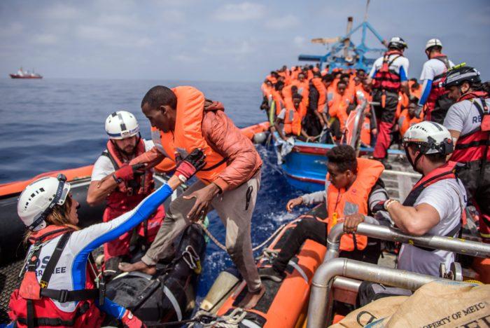 Földközi-tenger, 2018. április 21. Afrikai migránsnak segítenek gumicsónakba szállni az illegális bevándorlók tengeri mentését végzõ SOS Mediterranee civil szervezet Aquarius nevû hajója legénységének tagjai a Földközi-tengeren 2018. április 21-én. Az Aquarius mintegy 250 csónakban utazó illegális bevándorlót vett a fedélzetére a líbiai partoktól mintegy 50 kilométerre. (MTI/EPA/Christophe Petit Tesson)