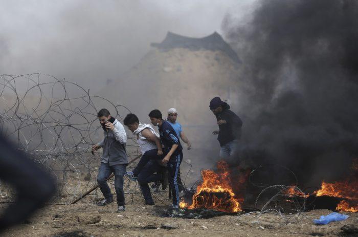 Izraeli-palesztin határ, 2018. április 27. Palesztin tüntetõk az izraeli katonák által helyezett szögesdrótkerítés közelében sûrû fekete füsttel égõ autógumik mellett az izraeli-gázai határon 2018. április 27-én. A Gázai övezetet uraló Hamász radikális iszlamista szervezet április eleji felhívására a palesztinok hat héten át tiltakoznak az izraeli blokád ellen, azt követelve, hogy visszatérhessenek földjeikre és otthonaikba, ahonnan a zsidó állam 1948-ban történt megalapításakor elûzték õket. (MTI/AP/Halil Hamra)
