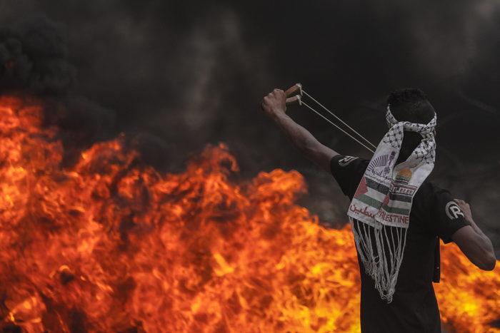 Gázai övezet, 2018. május 4. Palesztin tüntető csúzlival lő izraeli katonákra a Gázai övezet déli részén 2018. május 4-én. Az izraeli határ mellett a hatodik egymás utáni pénteken tartott tüntetésen százhetven palesztin megsebesült, az egyikük súlyosan. (MTI/EPA/Mohammed Szaber)