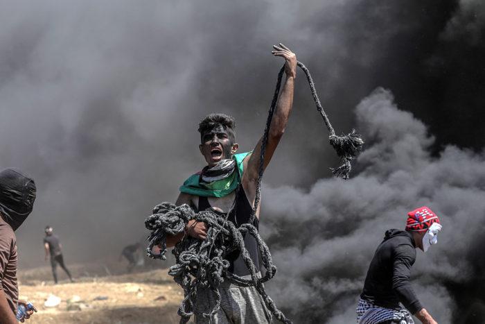 Gáza, 2018. május 14. Palesztin tüntető kötéllel a kezében égő gumiabroncsok füstjében az enklávét Izraeltől elválasztó kerítés mellett, Gáza városától keletre 2018. május 14-én. A nap folyamán több tízezer palesztin tiltakozott az amerikai nagykövetség Tel-Avivből Jeruzsálembe való átköltöztetése miatt. A palesztin egészségügyi hatóság összesítése szerint a Gázai övezet határán zajló összecsapásokban 52 palesztin vesztette életét, s több mint kétezren megsérültek. Az izraeli katonák könnygázzal és éles lőszerrel válaszoltak a palesztinok kerítést megközelítésére tett kísérleteire.(MTI/EPA/Mohammed Szaber)