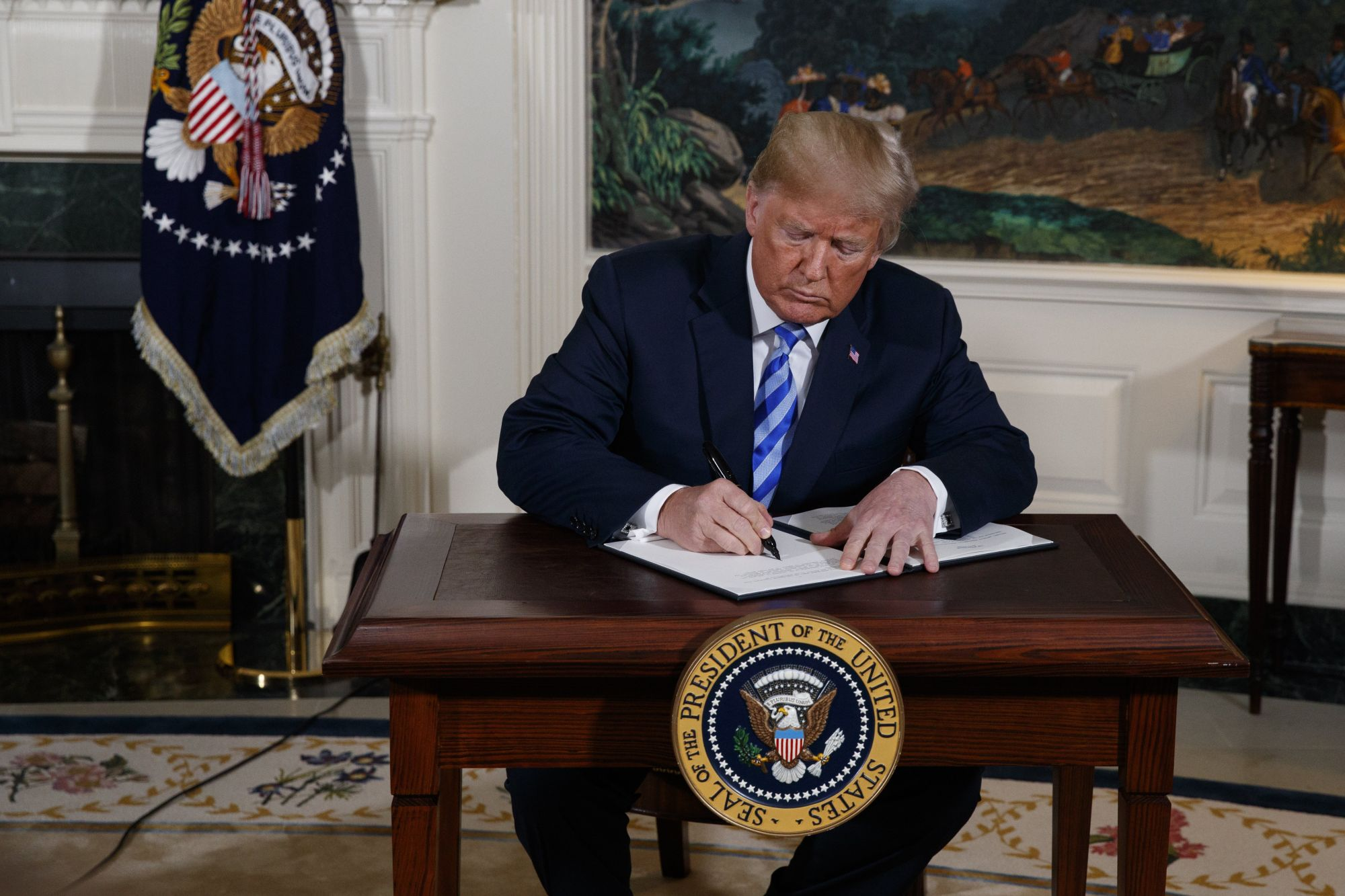 Donald Trump amerikai elnök rendeletet ír alá Irán elleni szankciók visszaállításáról a washingtoni Fehér Házban 2018. május 8-án, miután bejelentette, hogy az Egyesült Államok kilép az iráni atomprogramról 2015-ben aláírt többhatalmi szerződésből. (MTI/AP/Evan Vucci)
