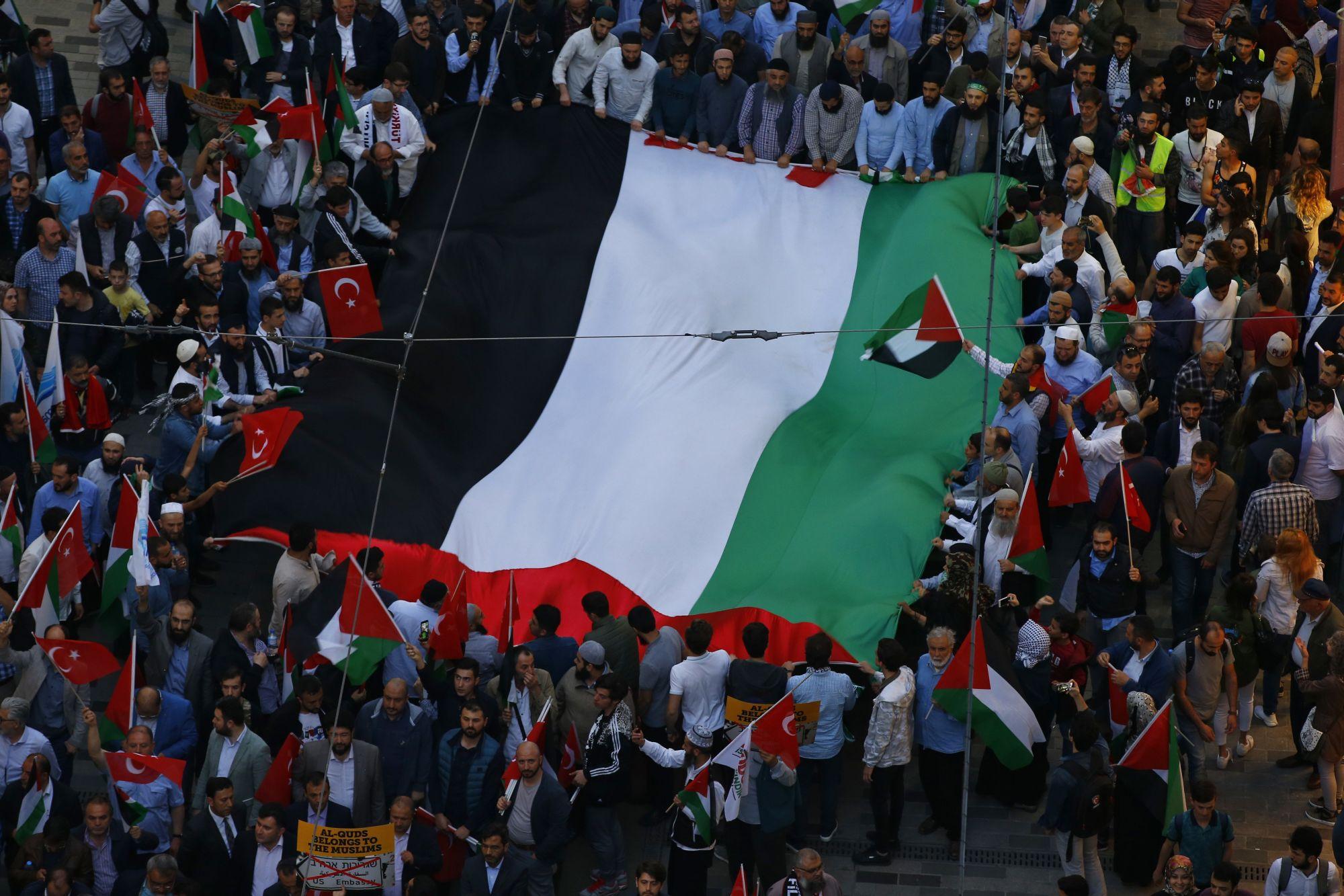 Óriási palesztin zászlót feszítenek ki tüntetőők Isztambulban, tiltakozásul az amerikai nagykövetség Tel-Avivból Jeruzsálembe való áthelyezése ellen 2018. május 14-én. Az Egyesült Államok a képviselet átköltöztetésével kifejezésre juttatta, hogy Jeruzsálemet ismeri el Izrael fővárosaként. (MTI/AP/Emrah Gurel)